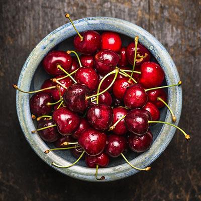 Cherries berries in blue bowl on dark rustic wooden background
