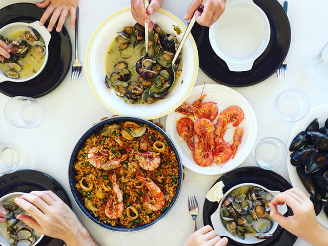 Family eating Paella and seafood. Top view.