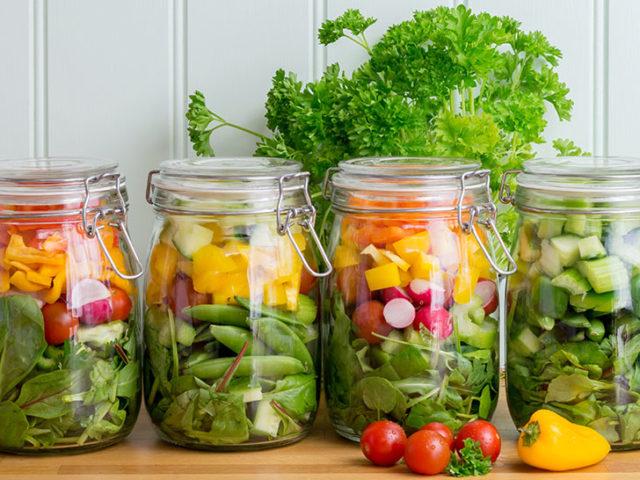Salad in glass storage jars. Four in a neat row.