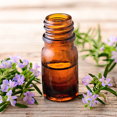 Rosemary massage oil and flowers on the wooden table
