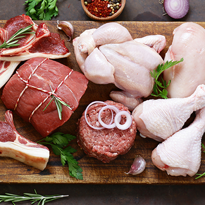 raw meat assortment – beef, lamb, chicken on a wooden board