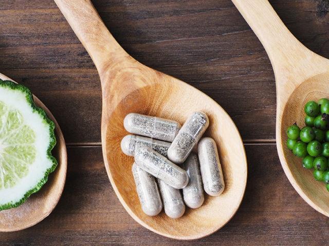 herbal pills in wooden spoon