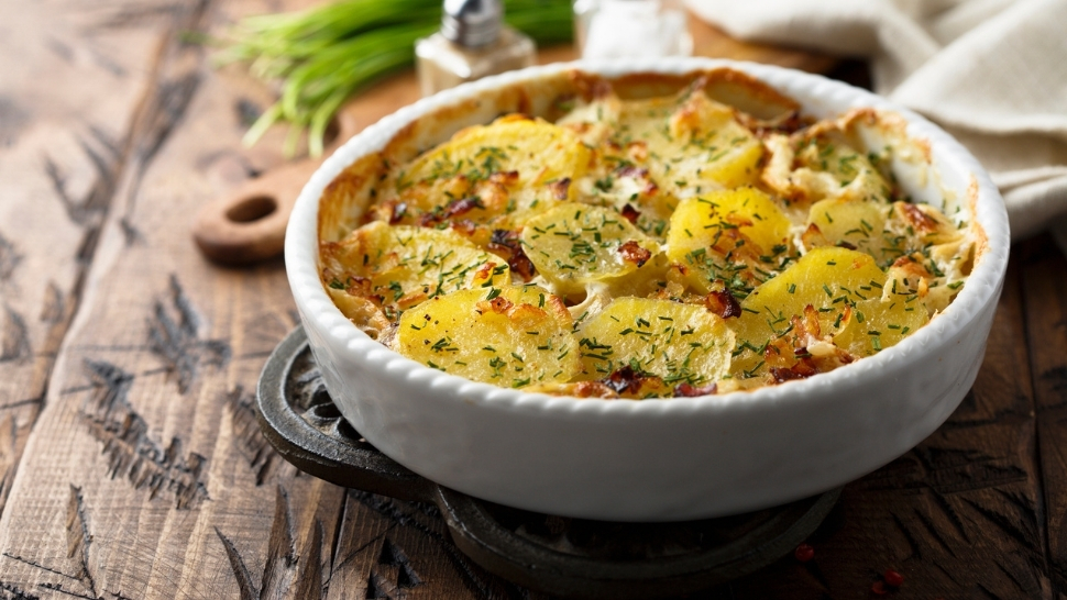 au gratin potatoes with cashew sauce in a white baking dish on a wooden table