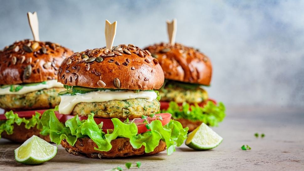 Photo of chickpea burger with lettuce tomato and sauce on seeded bun